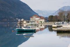 钓鱼有房子和山的木小船 免版税图库摄影
