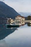 钓鱼有房子和山的木小船 免版税库存照片