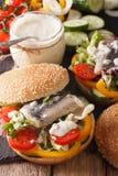 钓鱼汉堡用用卤汁泡的鲱鱼、小汤和新鲜蔬菜c 库存照片