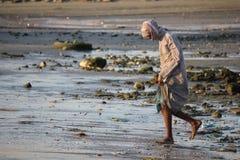 钓鱼注销海滩的卖主在日落 免版税库存照片