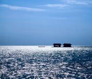 钓鱼海洋的剪影一点房子 免版税库存图片