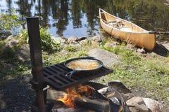 钓鱼烹调户外在有一个独木舟的一个煎锅在backgr 库存图片