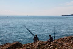 钓鱼由峭壁的人们 库存图片