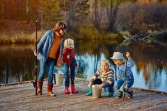 钓鱼的孩子观看朋友的抓住 木码头,秋天晴朗的天气 免版税库存图片
