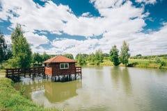 钓鱼的木小屋在小湖或河附近 库存图片