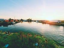 钓鱼的汽艇被栓对一个木浮码头 在村庄,蓝色海湾的小口岸 库存照片