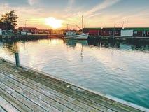 钓鱼的汽艇被栓对一个木浮码头 在村庄,蓝色海湾的小口岸 图库摄影