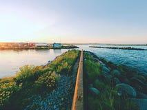 钓鱼的汽艇被栓对一个木浮码头 在村庄,蓝色海湾的小口岸 免版税图库摄影
