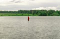 钓鱼的诱饵 垂悬在湖的背景的一钓鱼线的晃摇物 免版税库存照片