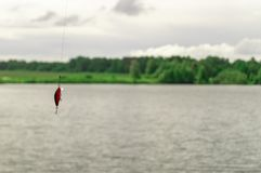 钓鱼的诱饵 垂悬在湖的背景的一钓鱼线的晃摇物 免版税图库摄影
