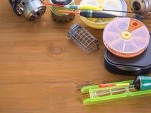 钓鱼竿、浮游物和箱子诱饵的在木背景 库存照片