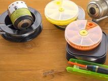 钓鱼竿、浮游物和箱子诱饵的在木背景 免版税库存照片