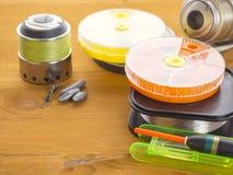 钓鱼竿、浮游物和箱子诱饵的在木背景 库存图片