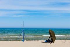 钓鱼竿和帐篷在海岸 免版税库存照片