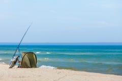 钓鱼竿和帐篷在海岸 库存照片