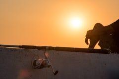 钓鱼竿和渔夫日落的 免版税库存图片