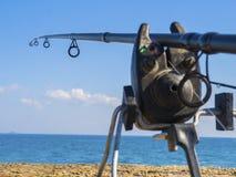 钓鱼竿和臭虫标志在海滨 免版税库存照片