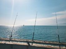 钓鱼竿等待咬住在码头 以航行游艇为背景 一个温暖的夏日 库存照片