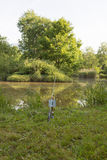 钓鱼竿,在湖的浮游物,上色了与一个地方的背景题字的 免版税库存图片