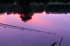 钓鱼竿reflexing的日落在河 库存图片