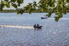 钓鱼者在一个晴朗的夏日去在寻找鱼的河的汽艇 库存图片