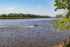 钓鱼者在一个晴朗的夏日去在寻找鱼的河的汽艇 免版税图库摄影