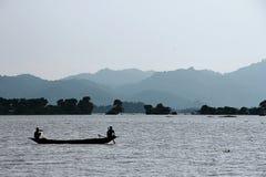 钓鱼者在日落时间附近的捕鱼湖 库存图片