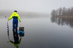 钓鱼者用在冰的捕鱼设备 图库摄影