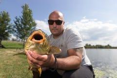 钓鱼者用鲤鱼渔战利品鲤鱼和渔夫,鲤鱼渔战利品 免版税库存图片
