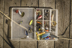 钓鱼诱剂和辅助部件在箱子在木背景 免版税库存图片