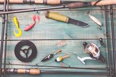 钓鱼象plunker小的主题的捕鱼在水之下 从钓鱼竿的框架有钓具的,线,刀子,卷轴和钓鱼浮体在绿色木背景 免版税库存图片