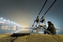 钓鱼都市编辑的夜 渔夫在有雾的夜 免版税库存照片