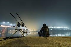 钓鱼都市编辑的夜 渔夫在有雾的夜 免版税库存图片