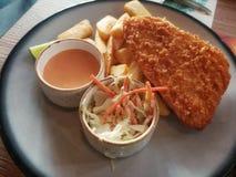 钓鱼酥脆牛排用提取乳脂的在白色盘油煎的沙拉和法语 免版税库存照片