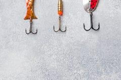 钓鱼钩和诱饵在一个集合抓的另外鱼在灰色背景与拷贝空间 r 图库摄影