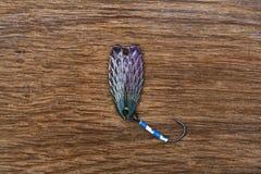钓鱼鳟鱼渔的诱剂在老木桌上 库存照片