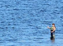 钓鱼从在水中的趟水者的一个人 免版税库存图片