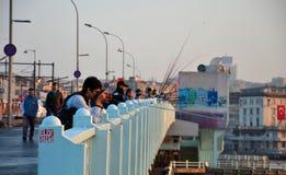 钓鱼从桥梁的摄影师和人们穿过Bosphorus海伊斯坦布尔土耳其 免版税库存照片