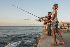 钓鱼Malecon日落哈瓦那的男孩 库存照片