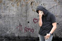 钛amo街道画和不快乐的男孩有黑有冠乌鸦的 库存图片