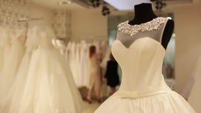 钝汉特写镜头与婚礼礼服,售货员的婚礼礼服为在一个新娘精品店的销售做准备 股票视频