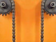 钝齿轮和双重链子在橙色背景与空的空间 库存照片