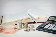 钞票、堆硬币和在一本开放书前面的一个计算器 昂贵的教育和低奖学金的概念 图库摄影