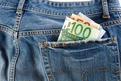 钞票一百,五十和二十黏附在后面牛仔裤外面的欧元装在口袋里 图库摄影