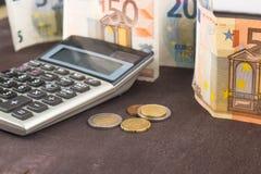 钞票和硬币与计算器 在木背景的欧洲钞票 税、赢利和费用的照片 库存照片
