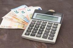 钞票和计算器 在木背景的欧洲钞票 税、借方和费用的照片 库存图片