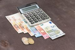 钞票和计算器 在木背景的欧洲钞票 税、赢利和费用的照片 免版税库存照片