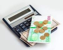 钞票在计算器、美元、欧元和硬币说谎 图库摄影