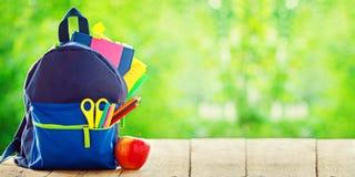 钞票 充分的学校背包用在木和自然绿色背景的苹果 免版税库存图片