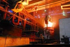 钢厂,有火炉busket的起重机 库存照片